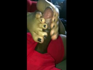 Girl with black toenails doing footjob for...