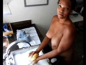 Naked and washing dishes with ebony housewife