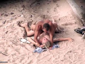 couple frolicking in the surf and rolling...